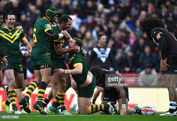 Trent Merrin of Australia celebrates scoring his team's third try with Johnathan Thurston and Cameron Smith during the Four Nations Final between New...