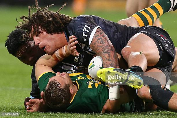 Trent Merrin of Australia gets tackled by Issac Luke and Kevin Proctor of New Zealand during the International Rugby League Test match between the...