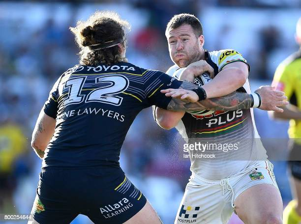 Trent Merrin of the Panthers is tackled by Ethan Lowe of the Cowboys during the round 16 NRL match between the North Queensland Cowboys and the...