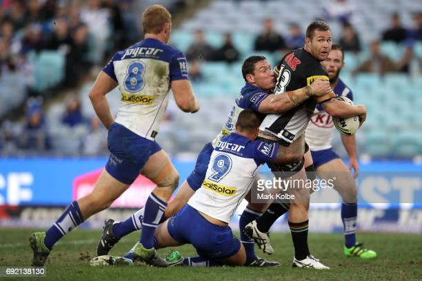 Trent Merrin of the Panthers looks to pass as he is tackled by Josh Jackson and Michael Lichaa of the Bulldogs during the round 13 NRL match between...