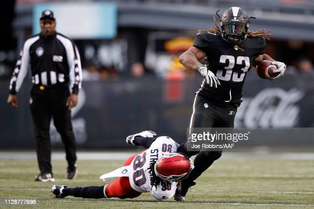 Trent Richardson of the Birmingham Iron is tripped up by Channing Stribling of Memphis Express during an Alliance of American Football game at Legion...