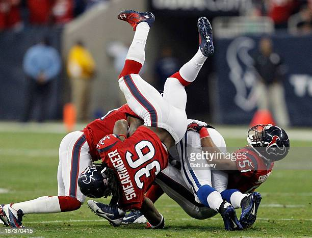 Trent Richardson of the Indianapolis Colts is tackled by DJ Swearinger of the Houston Texans Darryl Sharpton and Shiloh Keo at Reliant Stadium on...