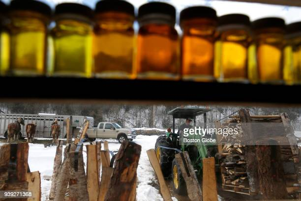 Trent Roleau uses a tractor to push a pallet of wood into the barn where he will use it to fire the evaporator that boils sap for maple sugar at The...