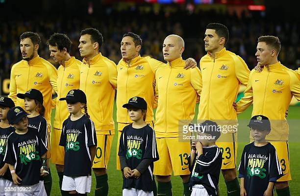 Trent Sainsbury Mark Milligan Tomas Rogic and Aaron Mooy of the Socceroos look on during the national anthems during the International Friendly match...