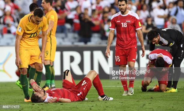 TOPSHOT Trent Sainsbury of Australia consoles Syrian Jehad Al Baour after Australia defeated Syria in their 2018 World Cup football qualifying match...