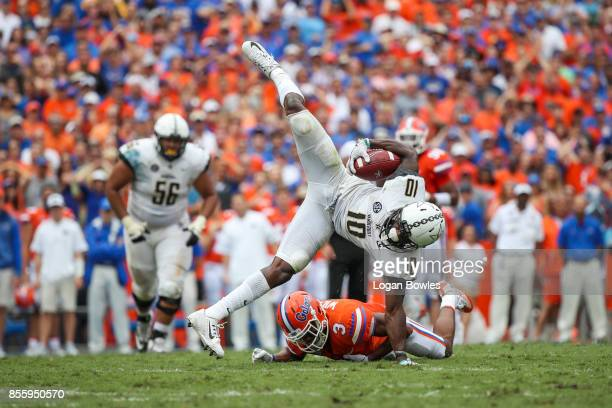 Trent Sherfield of the Vanderbilt Commodores makes a catch as Marco Wilson of the Florida Gators defends at Ben Hill Griffin Stadium on September 30...