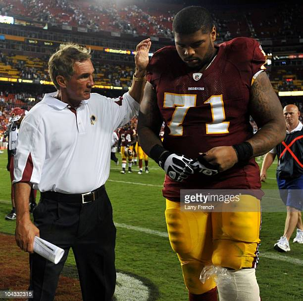 Trent Williams of the Washington Redskins is consoled by head coach Mike Shanahan during the game against the Houston Texans at FedExField on...
