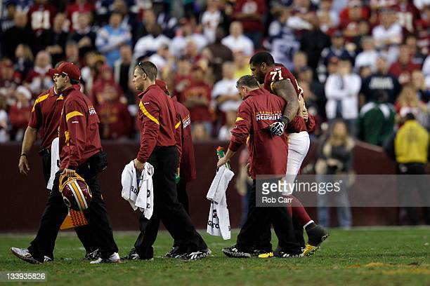 Trent Williams of the Washington Redskins is helped off the field after being injured against the Dallas Cowboys at FedExField on November 20 2011 in...