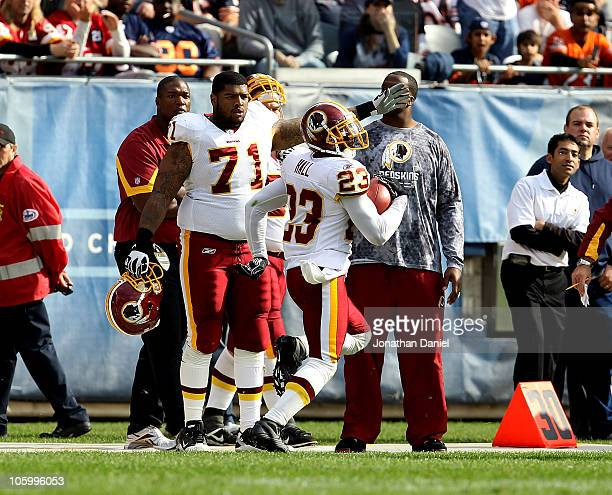 Trent Williams of the Washington Redskins points to the end zone as teammate DeAngelo Hall takes an interception in for a touchdown against the...