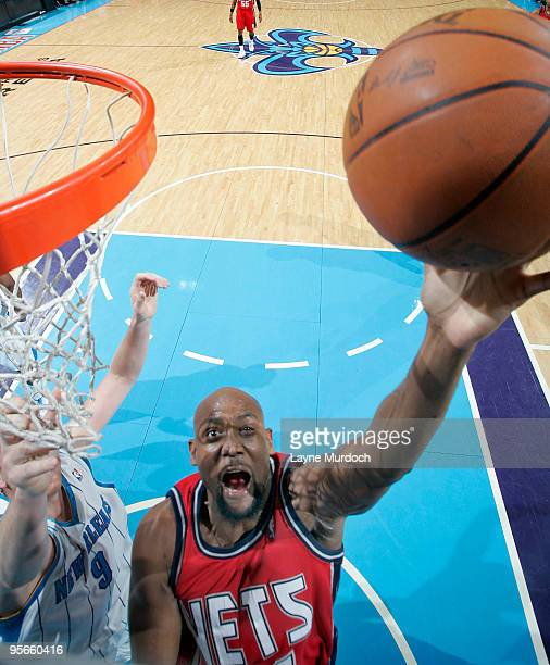 Trenton Hassell of the New Jersey Nets shoots over Darius Songaila of the New Orleans Hornets on January 8 2010 at the New Orleans Arena in New...