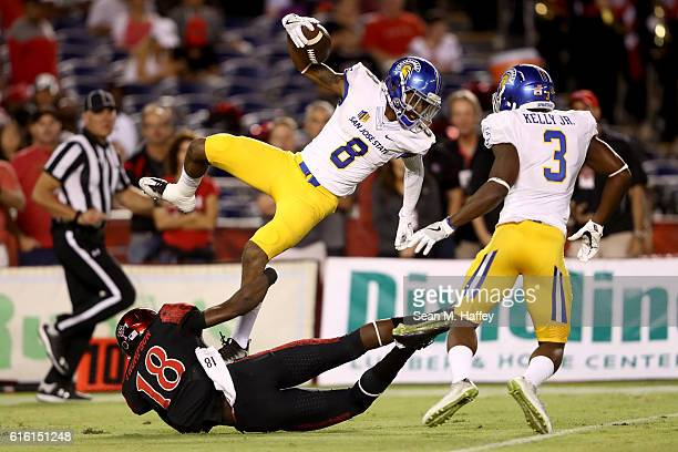 Trenton Thompson of the San Diego State Aztecs tackles Rahshead Johnson while Jermaine Kelly of the San Jose State Spartans looks on during the first...