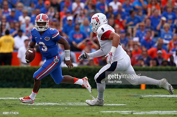 Treon Harris of the Florida Gators is defende by Trey Hendrickson of the Florida Atlantic Owls during the first half of the game at Ben Hill Griffin...