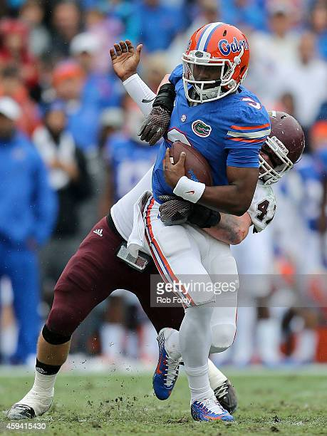 Treon Harris of the Florida Gators is pressured by Chris Kelly of the Eastern Kentucky Colonels during the first half of the game at Ben Hill Griffin...