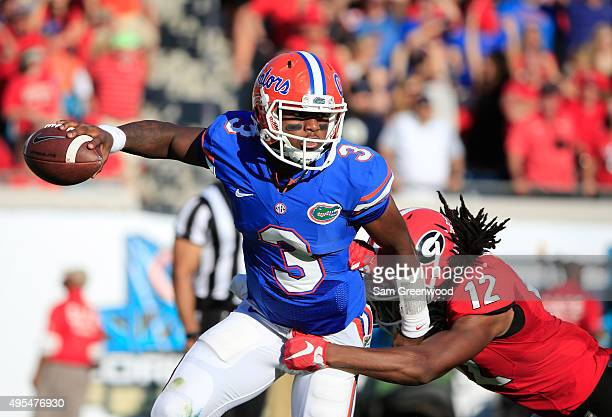 Treon Harris of the Florida Gators is pressured by Juwuan Briscoe of the Georgia Bulldogs during the game at EverBank Field on October 31 2015 in...