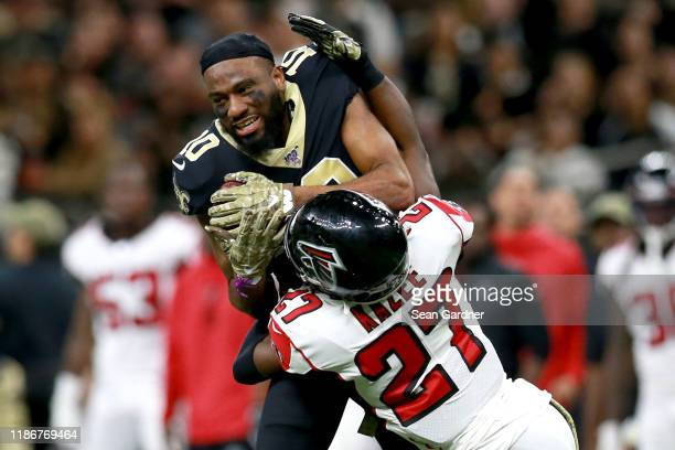 Tre'Quan Smith of the New Orleans Saints is tackled by Damontae Kazee of the Atlanta Falcons during a NFL game at the Mercedes Benz Superdome on...