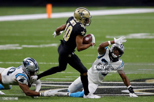 Tre'Quan Smith of the New Orleans Saints runs with the ball while being tackled by Jeremy Chinn and Troy Pride Jr. #25 of the Carolina Panthers in...