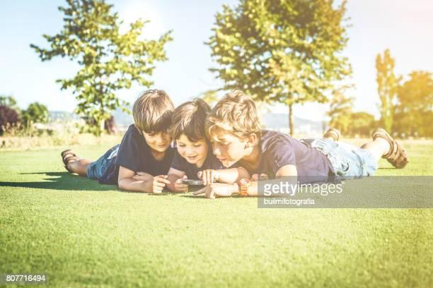 tres hermanos observando con lupa - três pessoas stock pictures, royalty-free photos & images