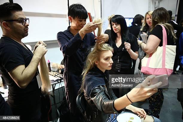TRESemme lead hair stylist Jeanie Syfu prepares a model backstage at TRESemme at Jenny Packham Bridal AW14 on April 11, 2014 at Industria Studios in...