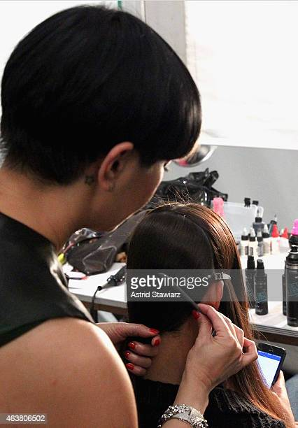 TRESemme lead hairstylist Jeanie Syfu prepares a model backstage at the TRESemme at Erin Fetherston fashion show during MercedesBenz Fashion Week...