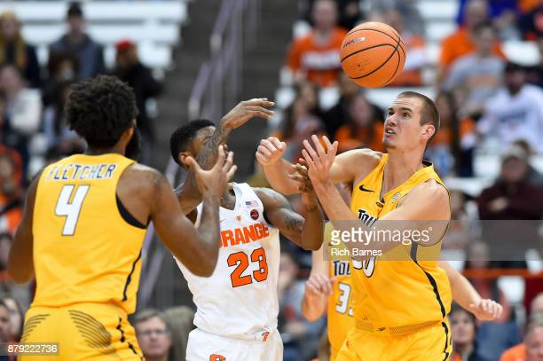 Tre'Shaun Fletcher of the Toledo Rockets Frank Howard of the Syracuse Orange and Luke Knapke of the Toledo Rockets react to a loose ball during the...