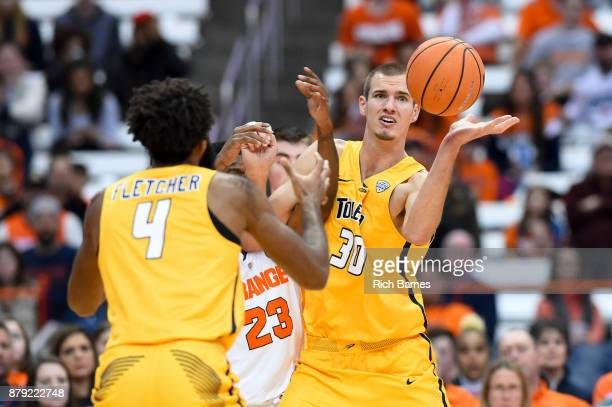 Tre'Shaun Fletcher of the Toledo Rockets Frank Howard of the Syracuse Orange and Luke Knapke of the Toledo Rockets battle for a loose ball during the...