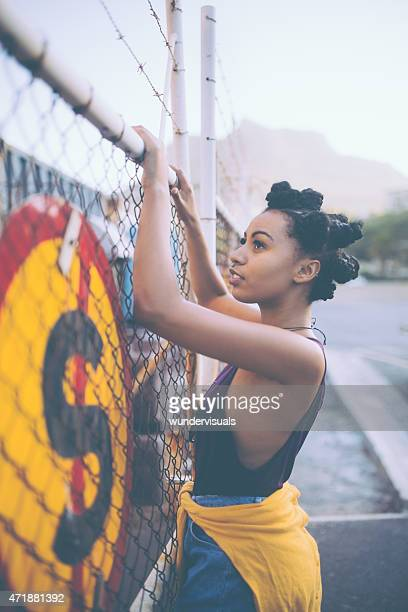 trespassing afro grunge girl climbing a fence - forbidden stock pictures, royalty-free photos & images