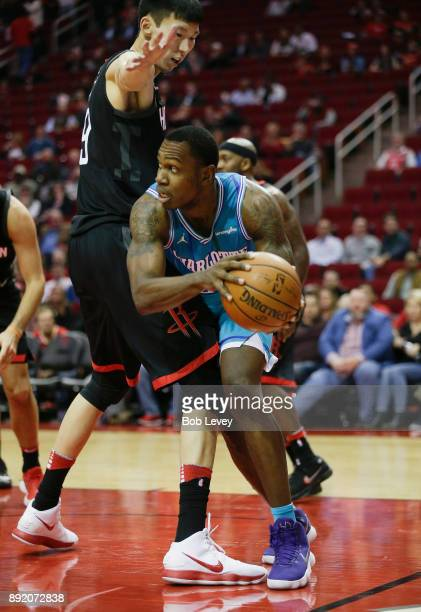 Treveon Graham of the Charlotte Hornets drives around Zhou Qi of the Houston Rockets in the fourth quarter at Toyota Center on December 13 2017 in...