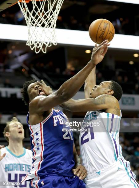 Treveon Graham of the Charlotte Hornets drives to the basket against Joel Embiid of the Philadelphia 76ers during their game at Spectrum Center on...
