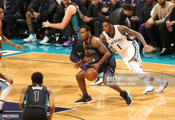 Treveon Graham of the Charlotte Hornets handles the ball against Jarell Martin of the Memphis Grizzlies on March 22 2018 at Spectrum Center in...