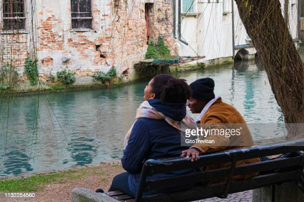 treviso -two young lovers sitting on the bank of the river sile - creole ethnicity stock pictures, royalty-free photos & images