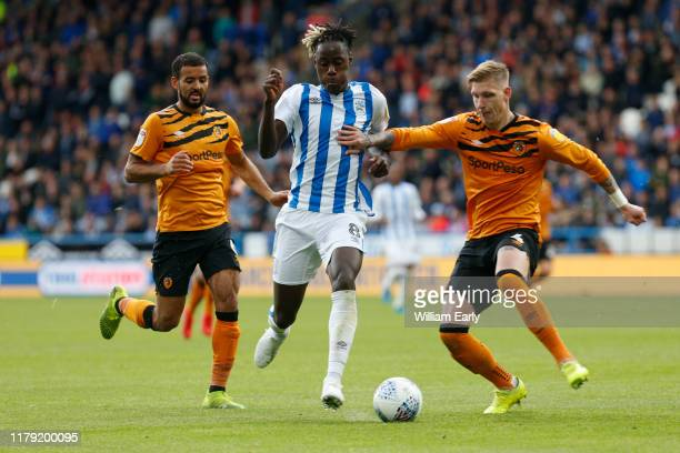 Trevoh Chalobah of Huddersfield Town takes on Jordy De Wijs and Kevin Stewart of Hull City during the Sky Bet Championship match between Huddersfield...