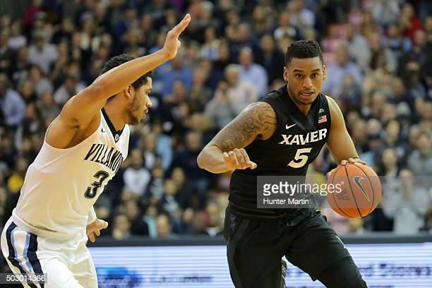 Trevon Bluiett of the Xavier Musketeers dribbles the ball as Josh Hart of the Villanova Wildcats defends during a game at the Pavilion on the campus...