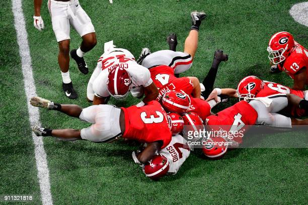 Trevon Diggs of the Alabama Crimson Tide is tackled by Roquon Smith Mecole Hardman and Christian Payne of the Georgia Bulldogs in the CFP National...