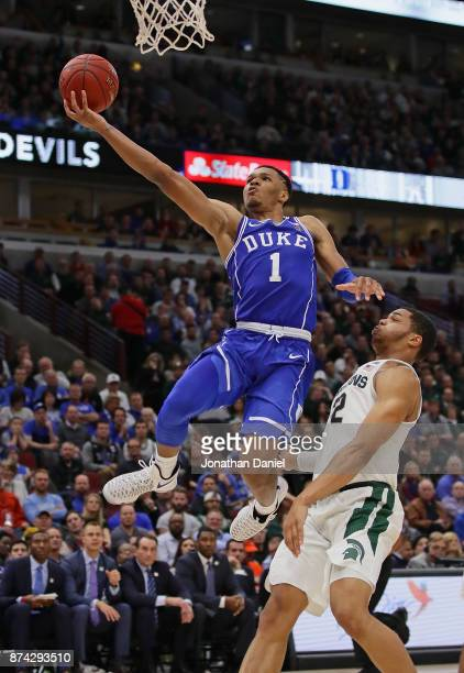 Trevon Duval of the Duke Blue Devils drives past Miles Bridges of the Michigan State Spartans during the State Farm Champions Classic at the United...