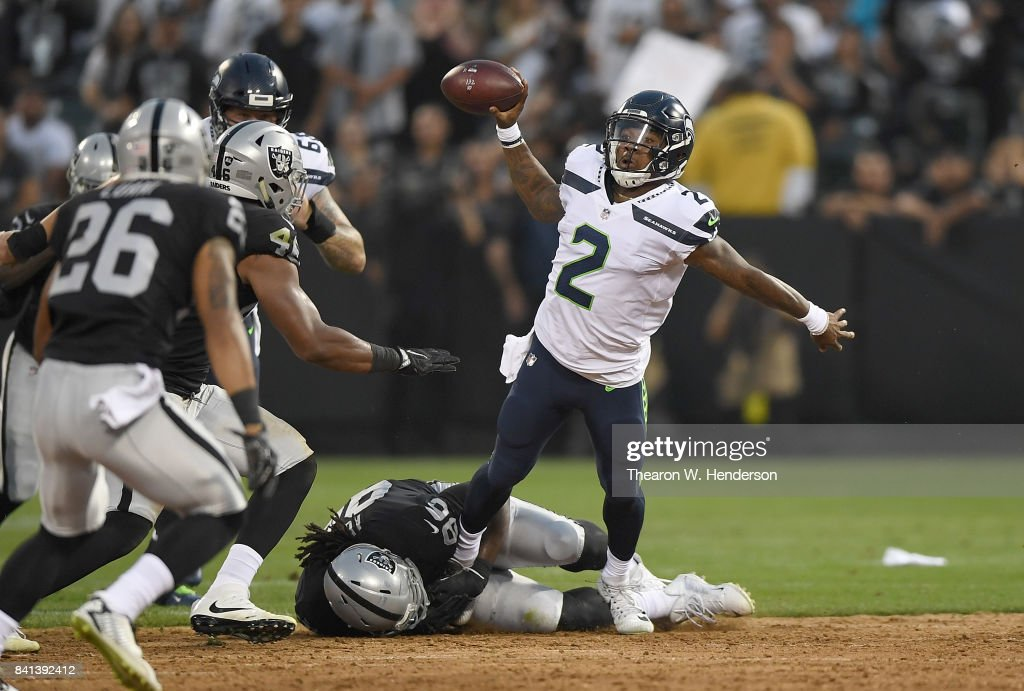 Trevone Boykin #2 of the Seattle Seahawks gets his pass off while being tackled by Denico Autry #96 of the Oakland Raiders during the first quarter of their game at the Oakland-Alameda County Coliseum on August 31, 2017 in Oakland, California.