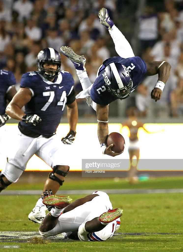 Trevone Boykin #2 of the TCU Horned Frogs is sent flying after being hit by Kyran Mitchell #11 of the Southern Methodist Mustangs as Halapoulivaati Vaitai #74 of the TCU Horned Frogs looks on in the second quarter at Amon G. Carter Stadium on September 19, 2015 in Fort Worth, Texas.