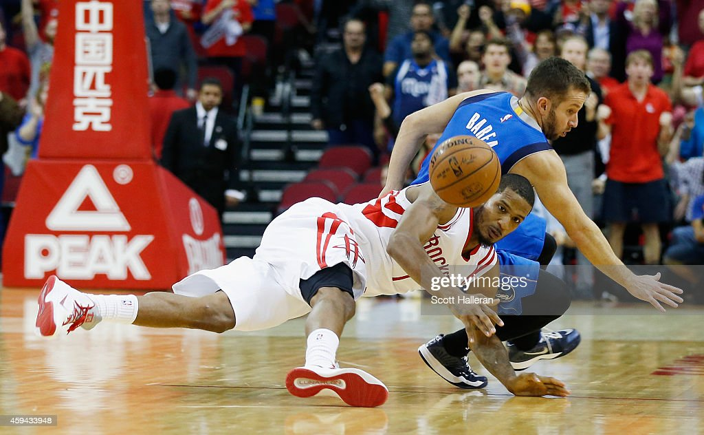 Trevor Ariza #1 of the Houston Rockets and J.J. Barea #5 of the Dallas Mavericks battle for a loose ball during their game at the Toyota Center on November 22, 2014 in Houston, Texas.