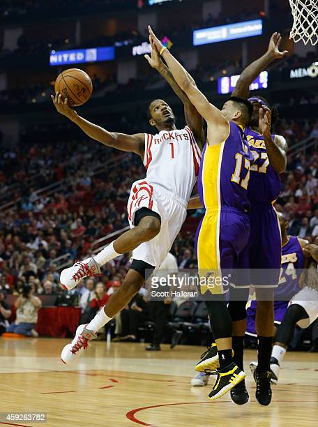 Trevor Ariza of the Houston Rockets takes a shot over Jeremy Lin and Jordan Hill of the Los Angeles Lakers during their game at the Toyota Center on...