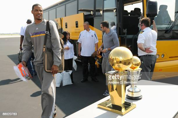 Trevor Ariza of the Los Angeles Lakers walks past the Larry O'Brien trophy and the Bill Russell MVP trophy on June 15 2009 in Los Angeles California...