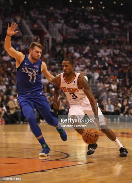 Trevor Ariza of the Phoenix Suns drives the ball past Luka Doncic of the Dallas Mavericks during the second half of the NBA game at Talking Stick...