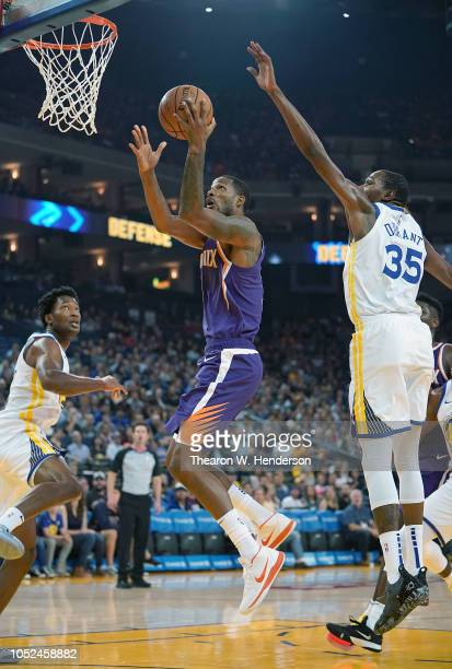 Trevor Ariza of the Phoenix Suns drives to the basket on Damian Jones and Kevin Durant of the Golden State Warriors during an NBA basketball game at...