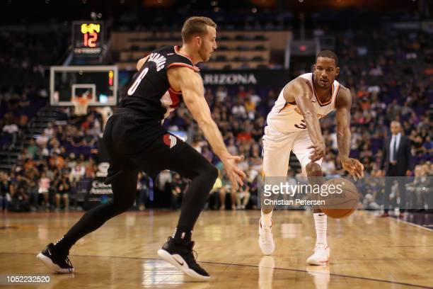 Trevor Ariza of the Phoenix Suns passes around Nik Stauskas of the Portland Trail Blazers during the NBA preseason game at Talking Stick Resort Arena...