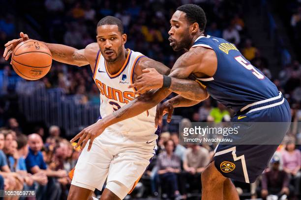 Trevor Ariza of the Phoenix Suns tries to dribble past Will Barton of the Denver Nuggets during the first half at Pepsi Center on October 20 2018 in...