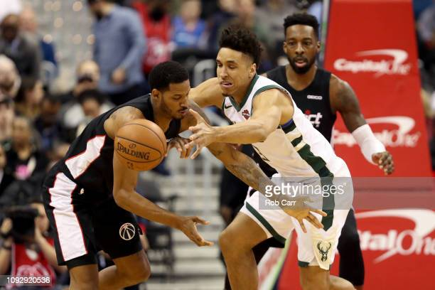 Trevor Ariza of the Washington Wizards and Malcolm Brogdon of the Milwaukee Bucks go after a loose ball in the first half at Capital One Arena on...