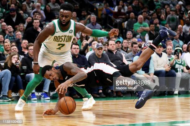 Trevor Ariza of the Washington Wizards dives in front of Jaylen Brown of the Boston Celtics for a loose ball during the second half of the game at TD...