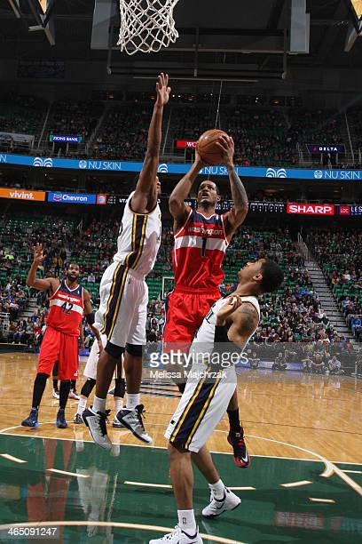 Trevor Ariza of the Washington Wizards shoots against Derrick Favors and Trey Burke of the Utah Jazz at EnergySolutions Arena on January 25 2014 in...