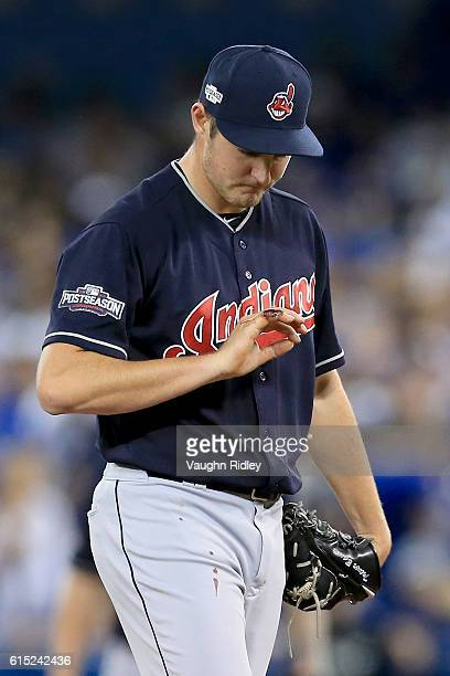 Trevor Bauer of the Cleveland Indians looks at his cut pinky finger in the first inning against the Toronto Blue Jays during game three of the...