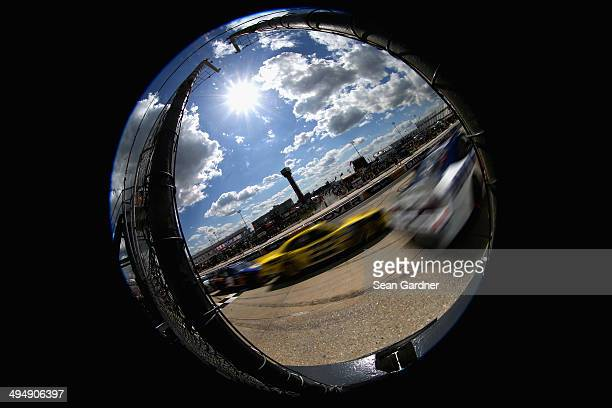 Trevor Bayne driver of the AdvoCare Ford leads Joey Logano driver of the Hertz Ford and Chase Elliott driver of the NAPA Auto Parts Chevrolet during...