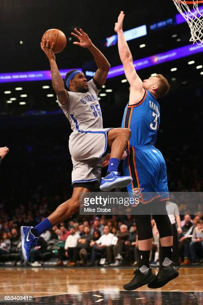 Trevor Booker of the Brooklyn Nets drives to the basket against Domantas Sabonis of the Oklahoma City Thunder at Barclays Center on March 14 2017 in...