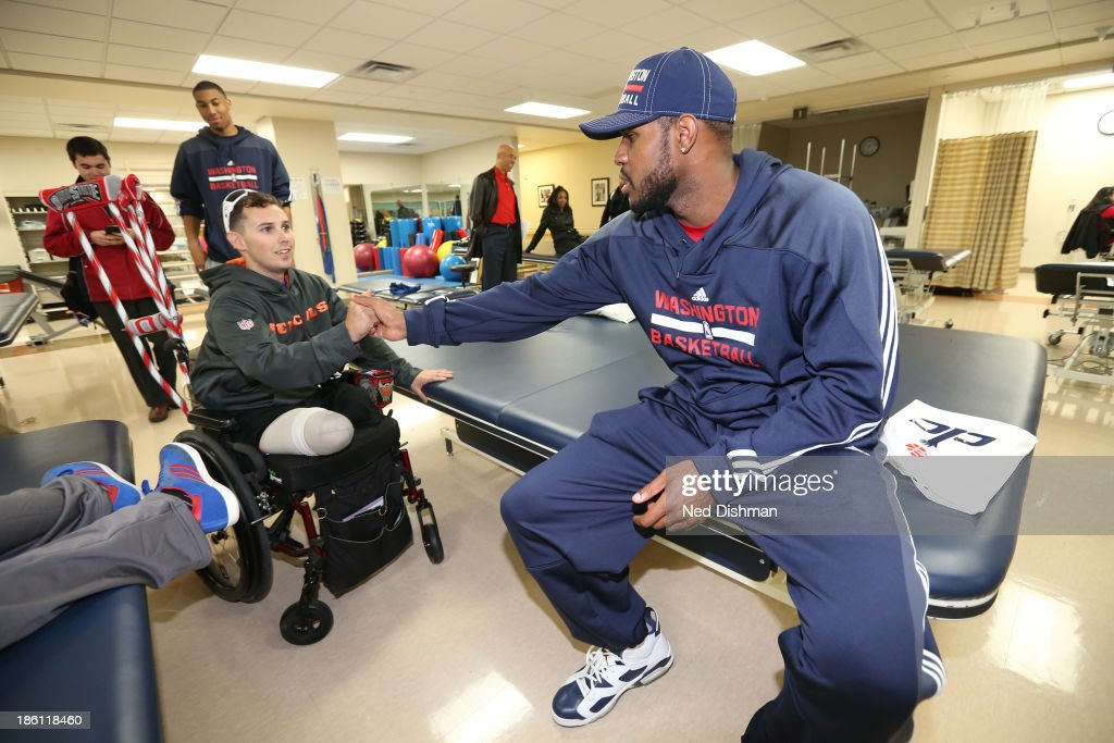 Trevor Booker #35 of the Washington Wizards greats a wounded warrior during a visit to Walter Reed Medical Center on October 25, 2013 in Washington, DC.